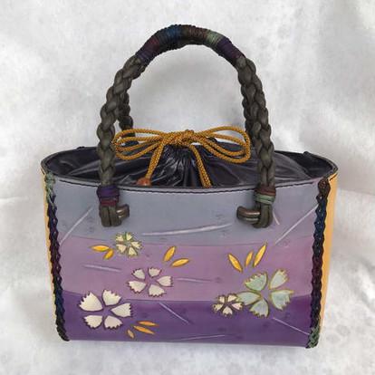 浴衣に合う軽めの和風バッグ。  正面・背面・サイドとも カワラナデシコの花を一部くり抜き、 中から白基調に仕上げた革を重ねて 立体的に仕立てました。  夏祭り、夜のお出かけ。 白い花が一層際だって見えます。  持ち手は直径6mmの丸紐を4本 編みして柔らかく仕上げました。  また、持ち手部分と綴じ紐は 藍・紺・エンジ・茶・焦茶・ モスグリーン・紫等、 和風の多色使いの紐を使用しました。  メリハリがつきつつ、 しかも馴染んで面白いです。  【サイズ】  バッグ・・タテ15.5cm×ヨコ23cm、       マチ9cm(底)→7.5cm(上部)  持ち手紐     ・・長さ30cm(バッグよりはみ出し分)       直径5mm紐を4本編み 【重 さ】251.5g  【使用材料】  表面・・成牛0.8mm 、1.2mm、      巾着部分=合皮(紫)、留め金具、      綴じ紐(ナイロン多色)、他  内面・・豚モミソフト(焦げ茶)      ポケット1コ