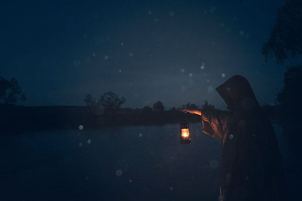 cloaked figure standing at a lake lantern