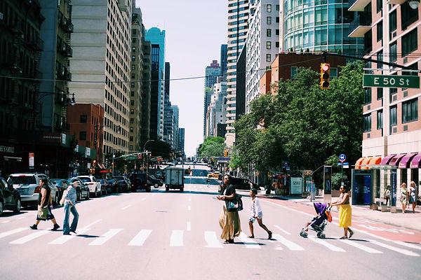 People walking cross walk city