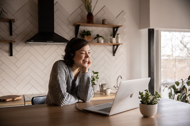 smiling-woman-talking-via-laptop-in-kitc