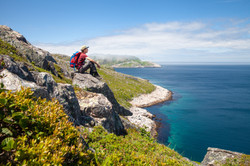 hiker sitting on coast