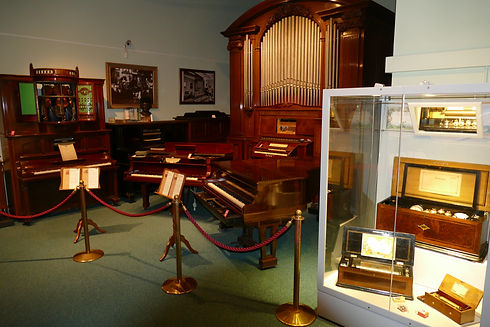 Interior of museum showing a large organ, 4 pianos and glass cabinet containing music boxes.