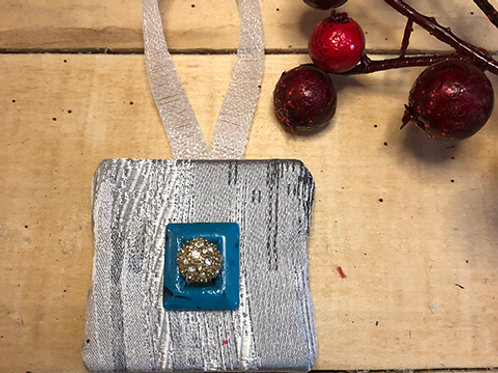 Silver Ornament with a blue button accent