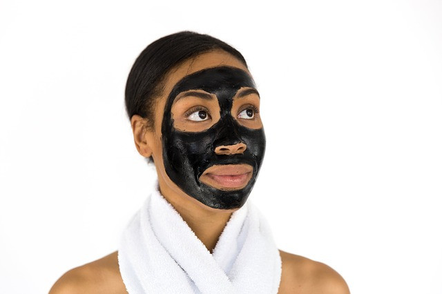 black girl with charcoal black face mask on for skincare