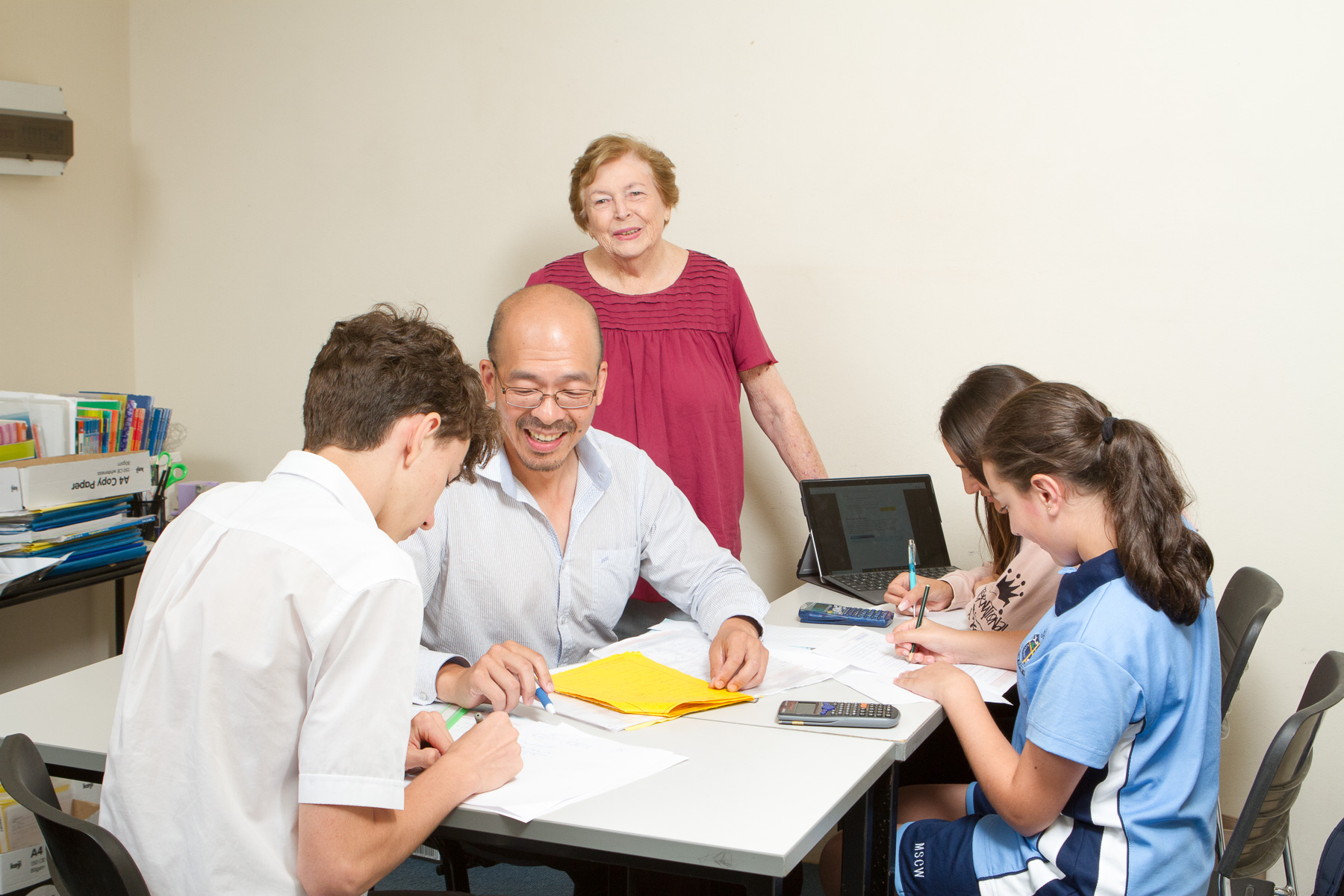 Founder Beryl Novice and head tutor Dwang with maths students doing an after school tuition session