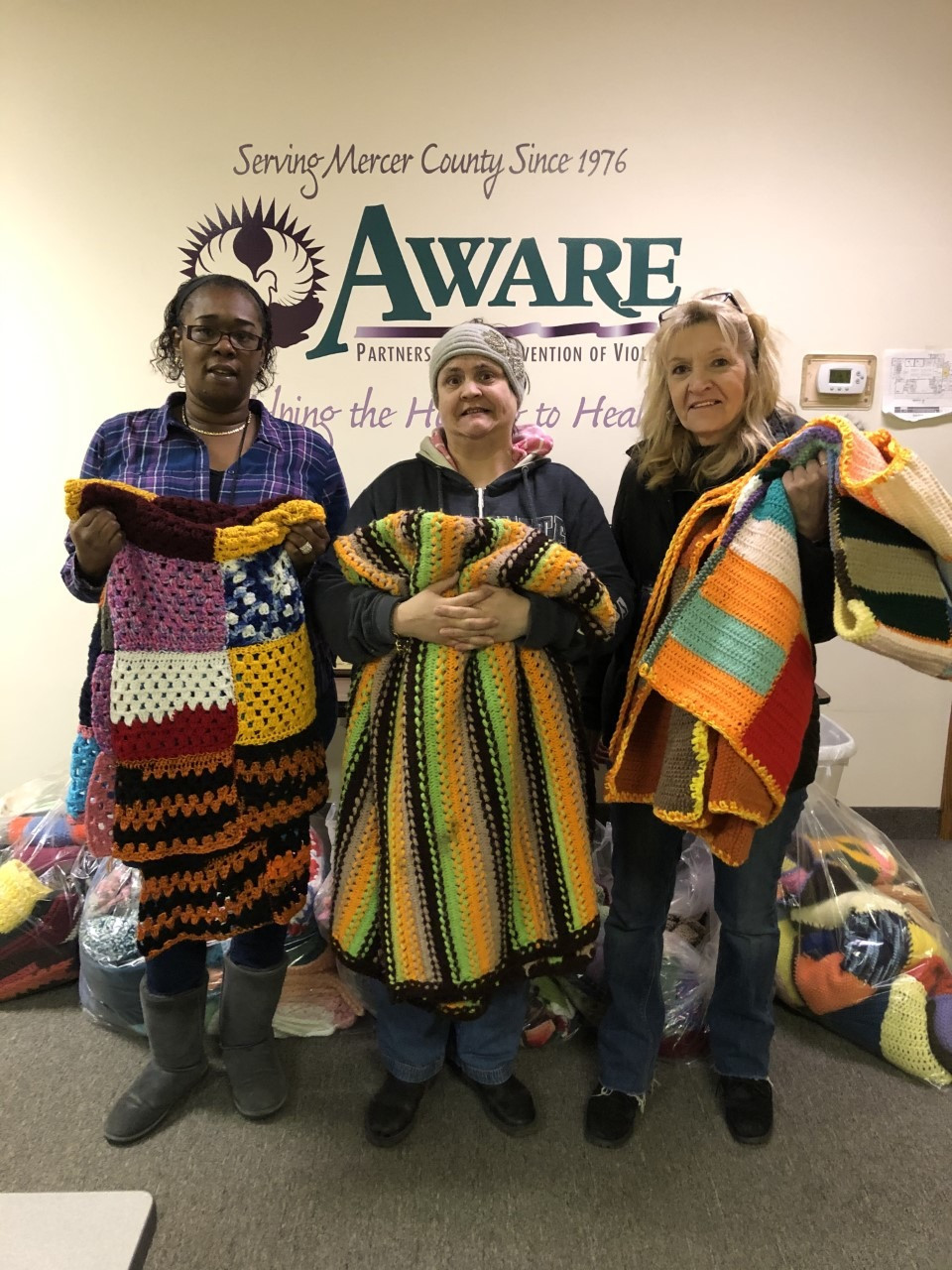AWARE advocate, Marise Wright (left), is presented handmade blankets from Darlene and Lorraine.