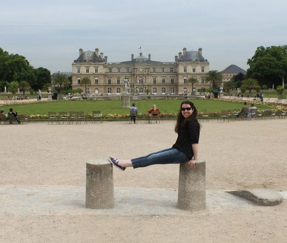 The author sitting atop two small stone pillars in front of the Luxembourg Palace in Paris