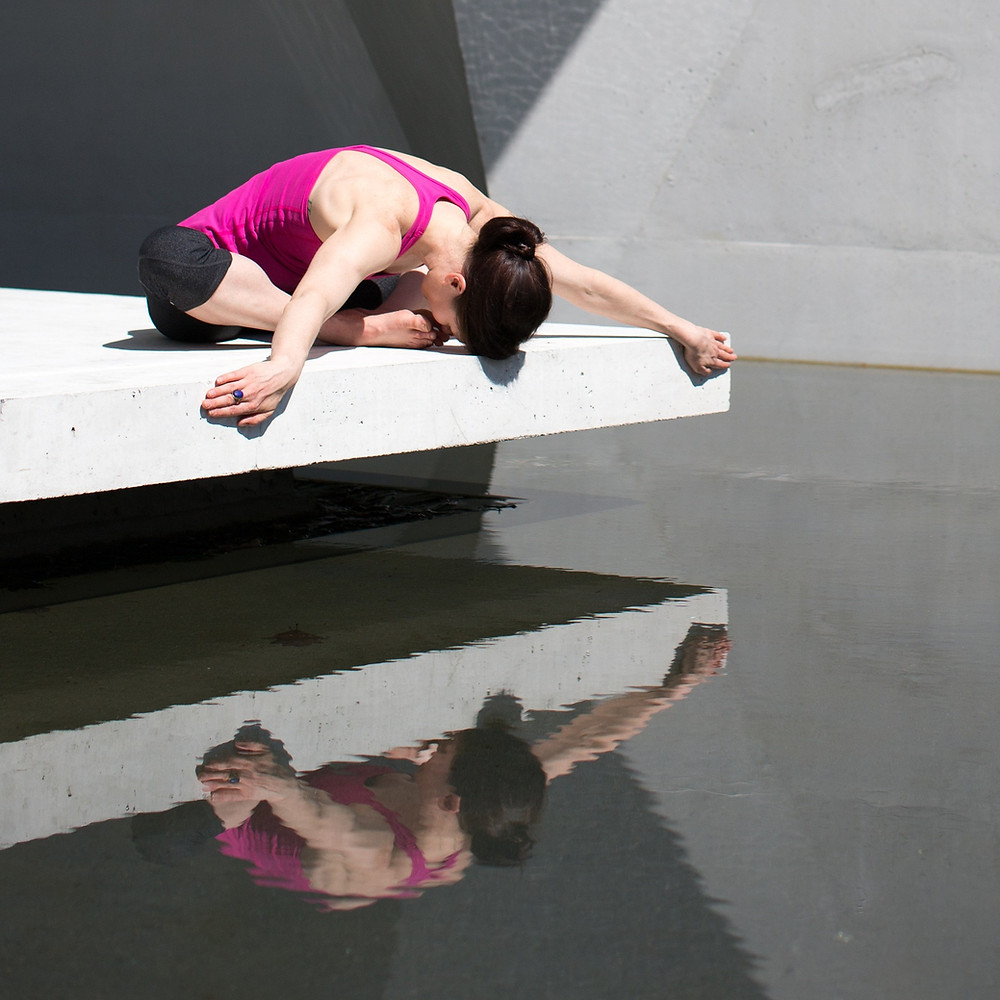 woman performing a yoga pose above a pool of water