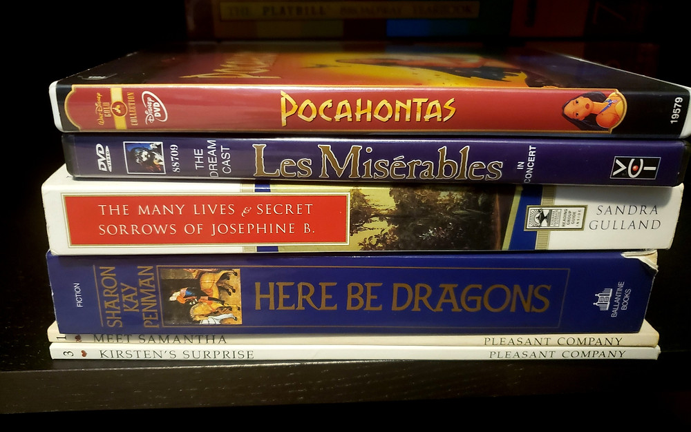 DVD spines of Disney's Pocahontas and the Les Miserables 10th anniversary concert above a selection of books: The Many Lives and Sorrows of Josephine B., Here Be Dragons, Meet Samantha, and Kirsten's Surprise