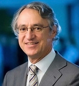 A photograph of Prof Jeffrey Zajac. He has wavy grey hair, is wearing glasses and a grey suit, and is smiling.