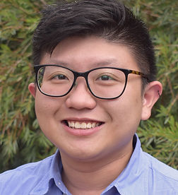 A photograph of Alex Wong. He is smiling, and is wearing glasses and a blue collared shirt.