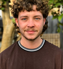 A photograph of Lucas Foster Skewis. He has a moustache and curly, brown hair, and is smiling.