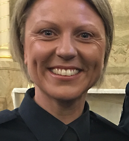 A photograph of Kylie King. She has short blonde hair, is wearing a dark collared shirt, and is smiling.