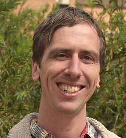 A photograph of Dr Lachlan Angus. He is wearing a flannel collared shirt, and is smiling.