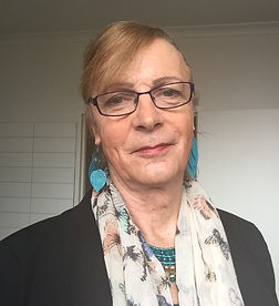 A photograph of Clare Headland. She is wearing blue earrings, a scarf with butterflies printed on it, and a pair of glasses. She is smiling.