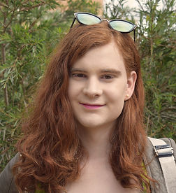 A photograph of Ariel Ginger. She has long red hair, earrings, and sunglasses. She is smiling.