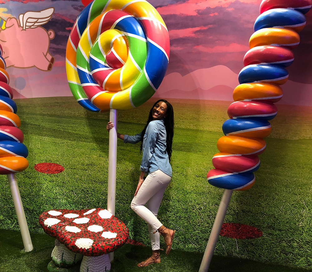 ShanMichele posing with life-sized lollipops at Candytopia.