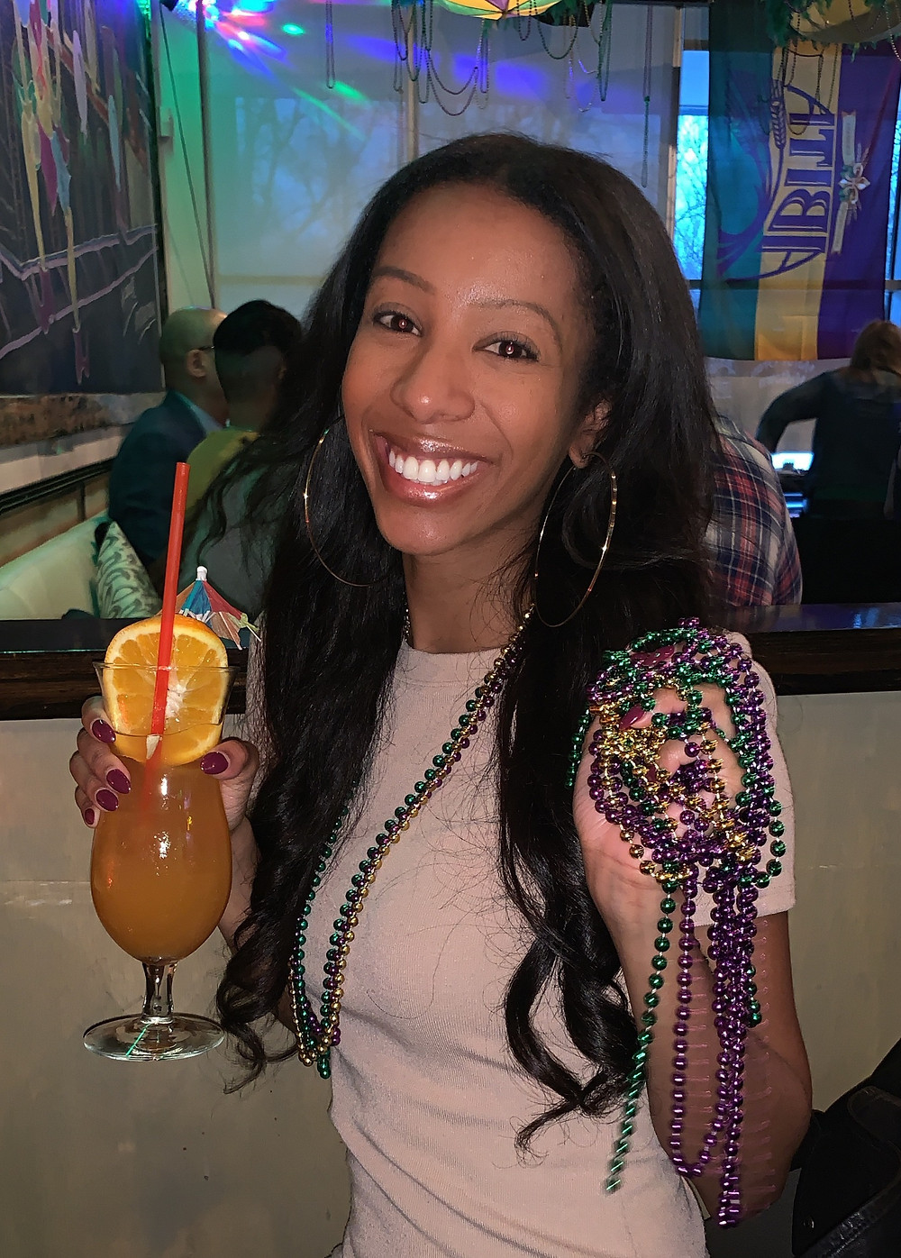 ShanMichele with a hurricane drink and Mardi Gras beads.