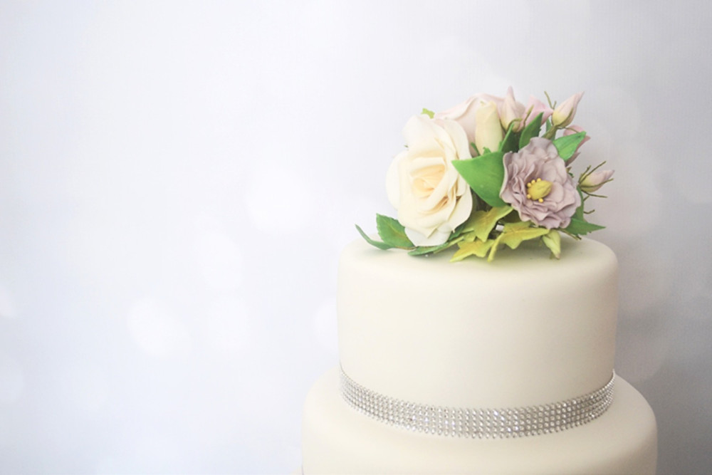 Top tier with diamante ribbon, cream roses, green ivy and lisianthus flowers and buds