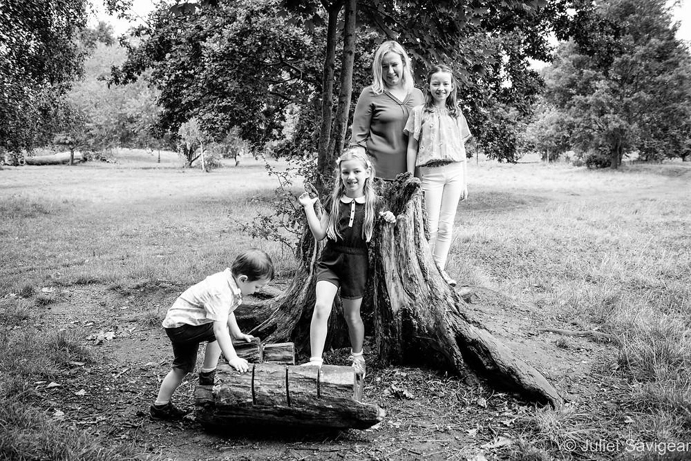Family playing around tree stump
