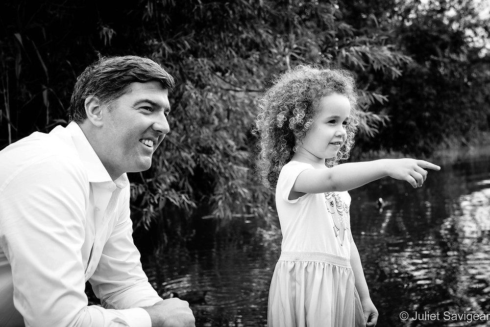 Father and daughter by the pond