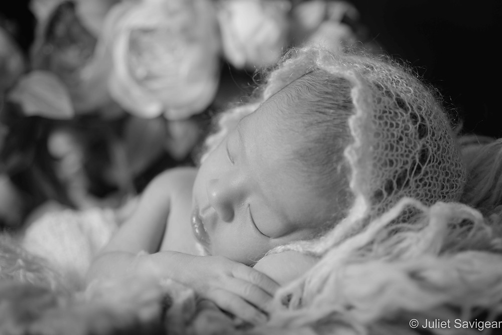Sleeping baby with bonnet and flowers