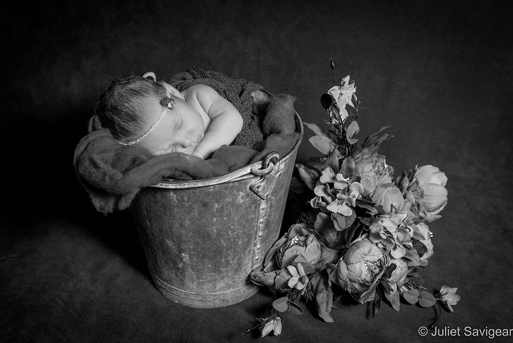 Baby in a bucket with flowers