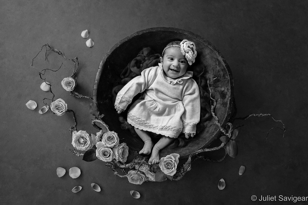 Baby in wooden bowl with roses