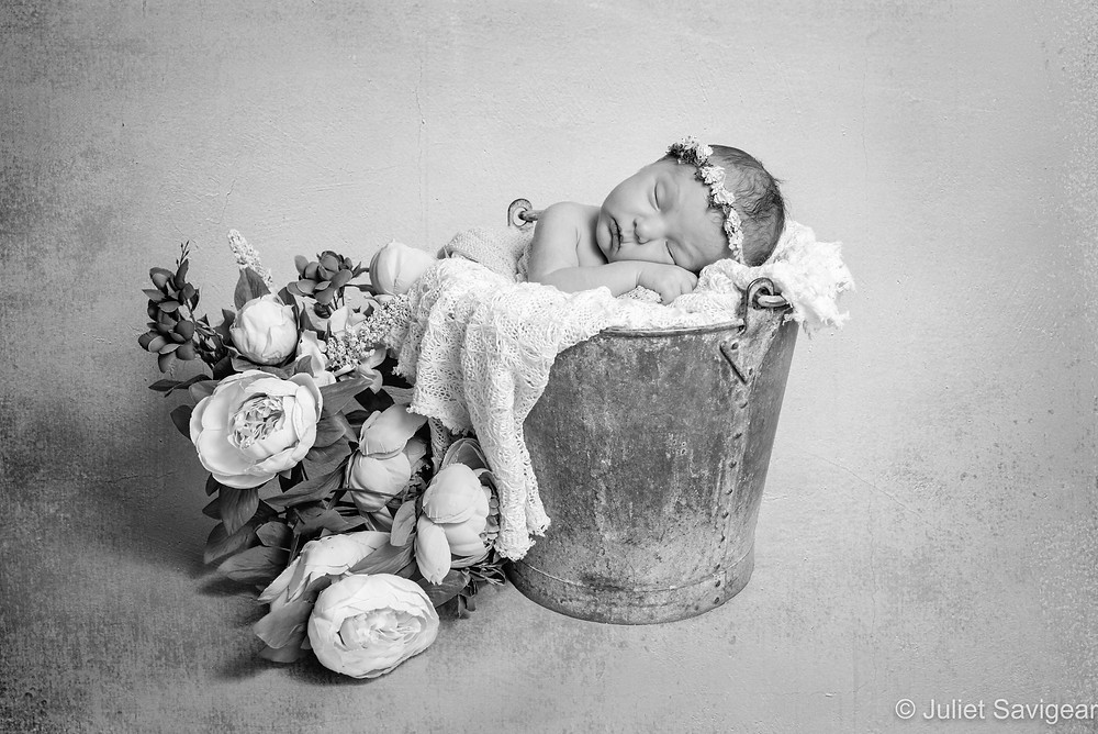 Sleeping baby in bucket with flowers