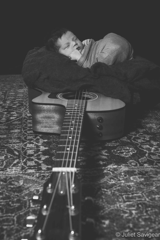 Baby sleeping on guitar