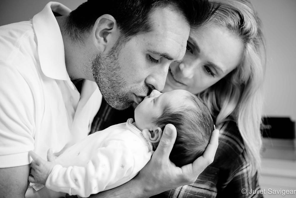 Family kisses for newborn baby