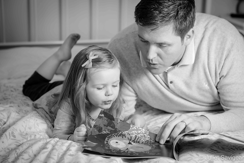 Daddy reading book with daughter