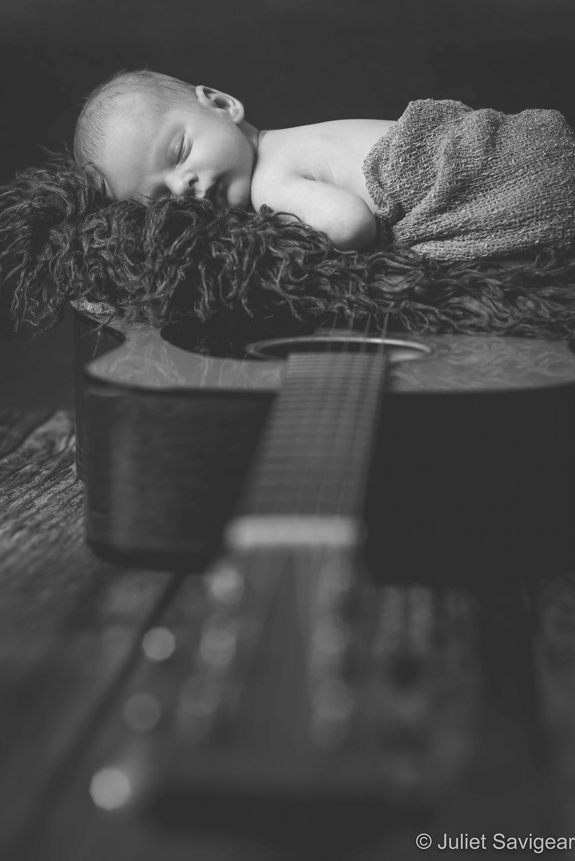 Newborn baby sleeping on guitar