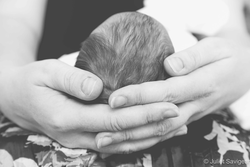 Baby's head cradled in hands