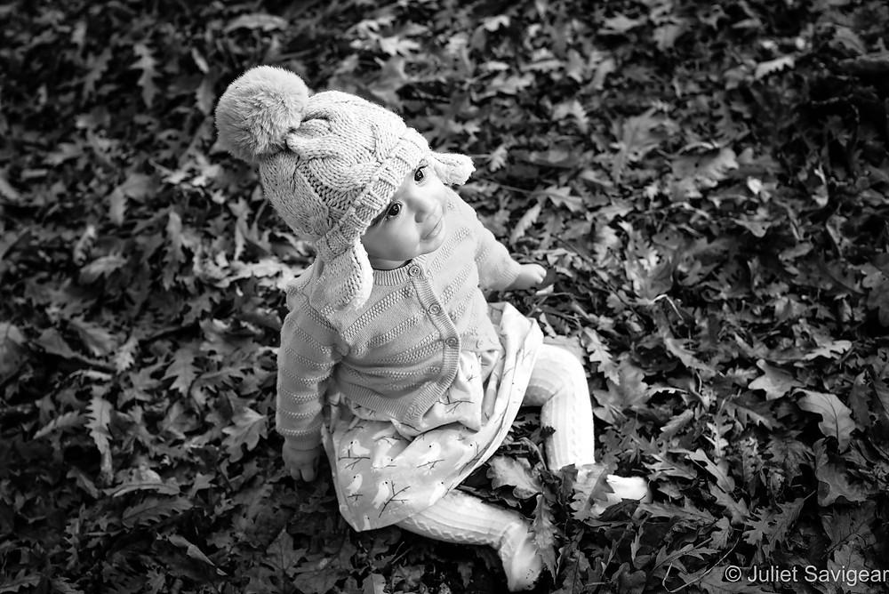 Baby girl among the oak leaves