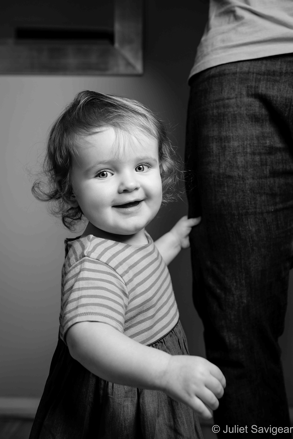 One year old holding onto daddy's leg