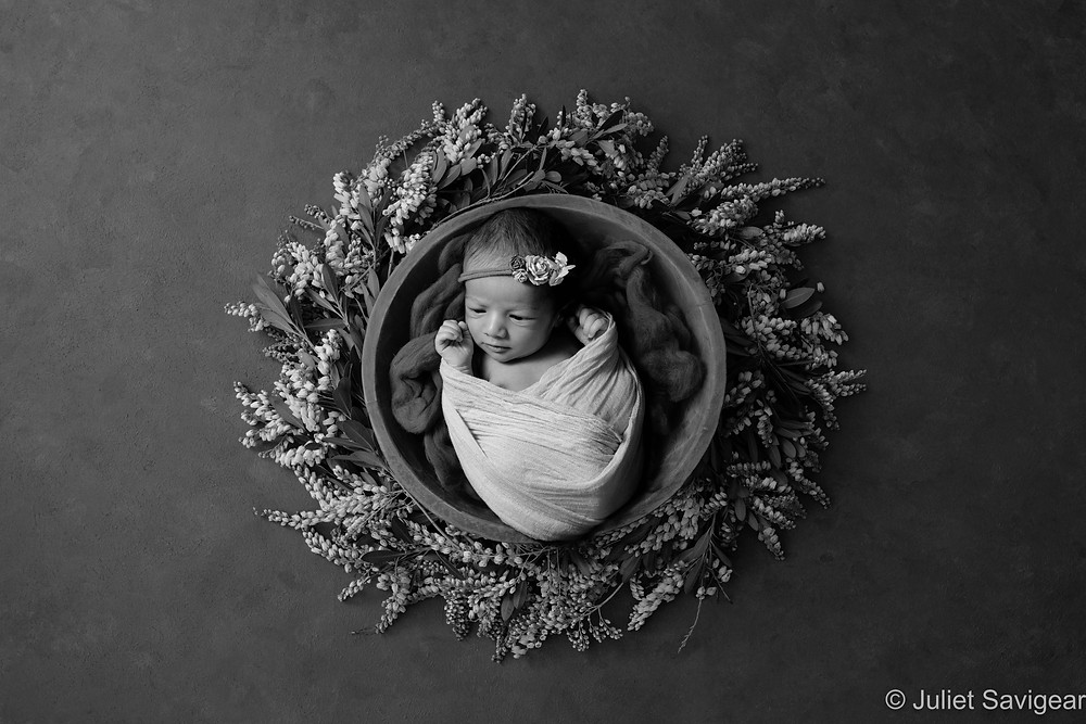 Newborn baby in floral wreath