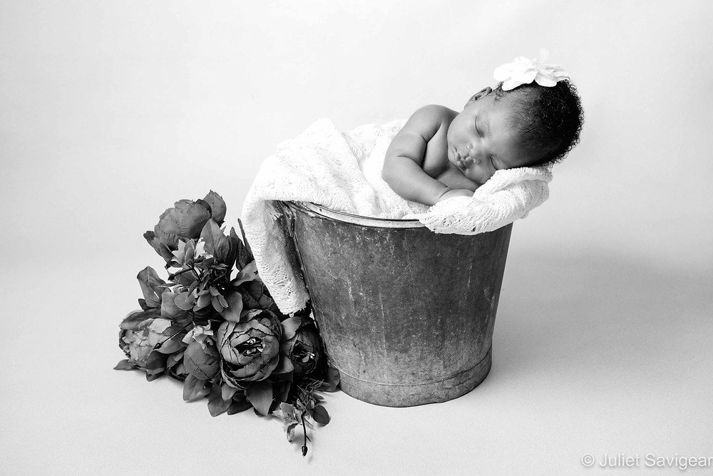 Newborn baby sleeping in bucket