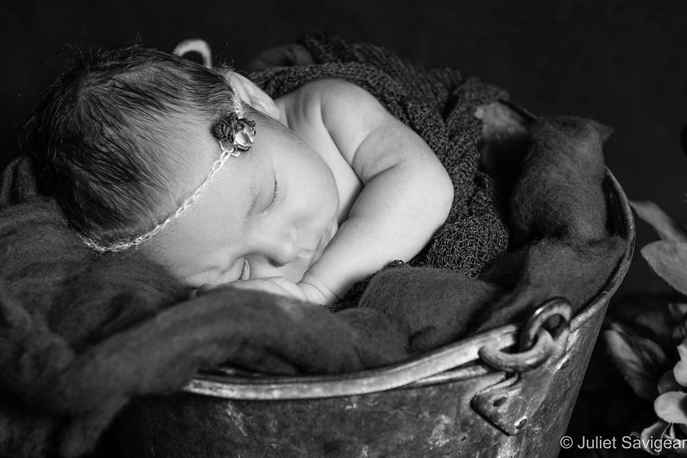 Close up on sleeping newborn in bucket