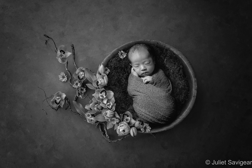 Newborn baby with beautiful orchids