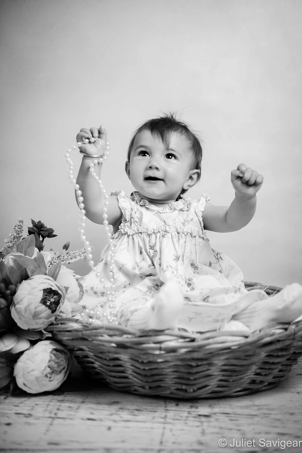 Baby girl in basket with flowers and beads