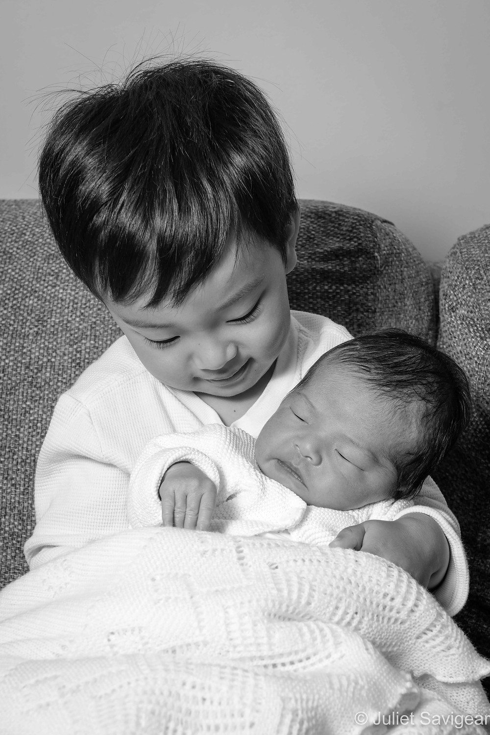 Baby sister in brother's arms