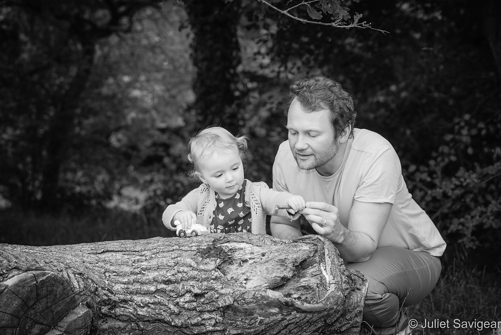 Father & daughter playing on log
