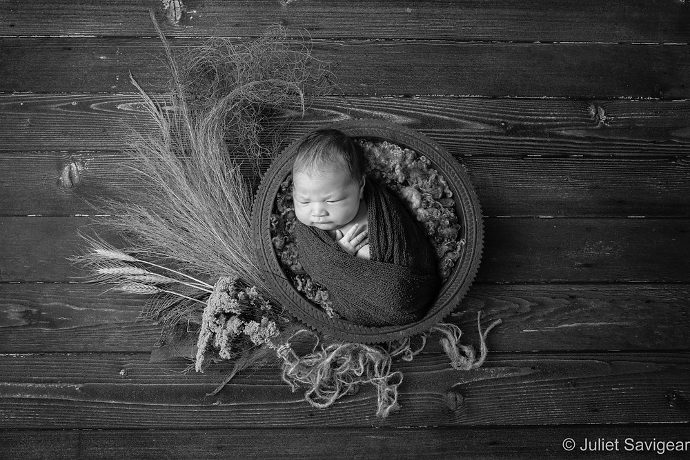 Baby girl in wooden bowl