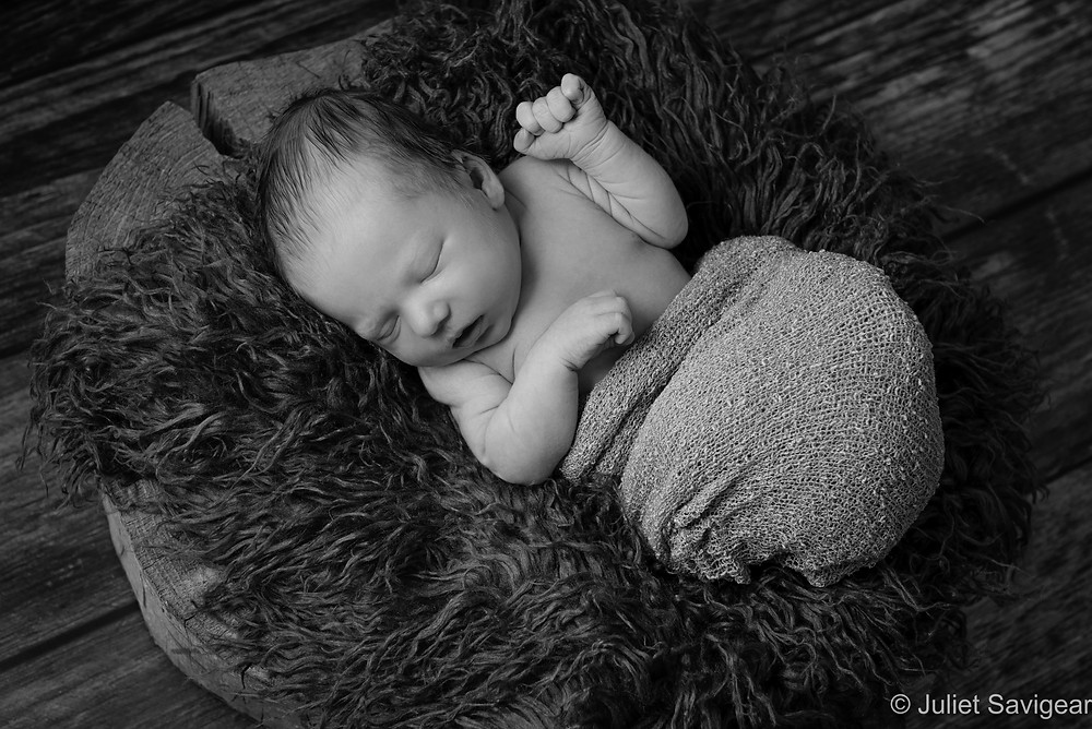 Newborn baby sleeping on wood block