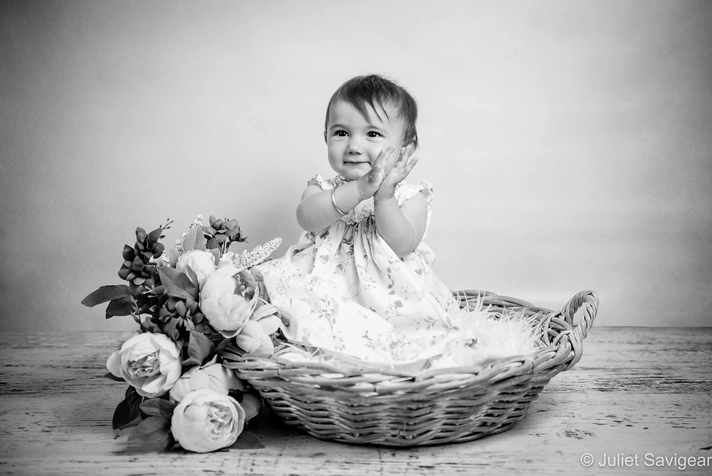 Baby girl in basket with flowers