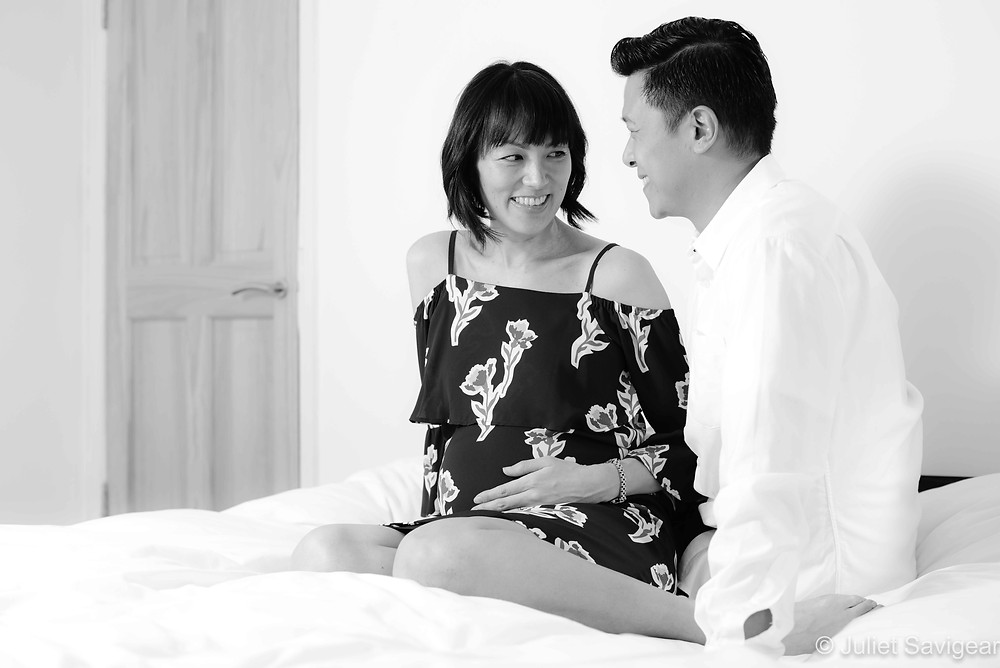 Pregnancy photo - couple sat on bed