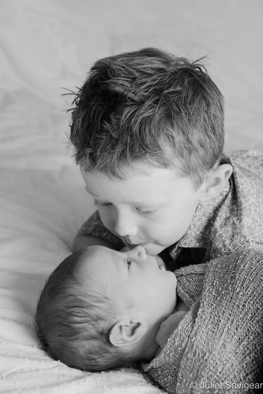 Brother kisses newborn baby