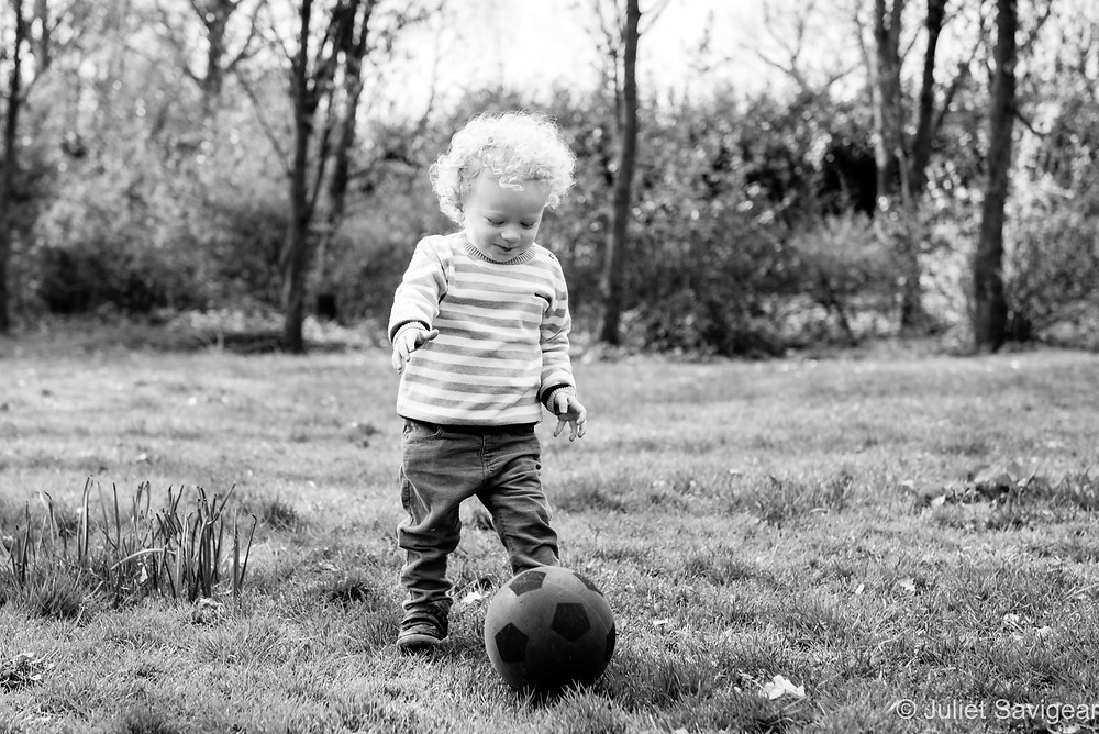 Toddler playing football in the park