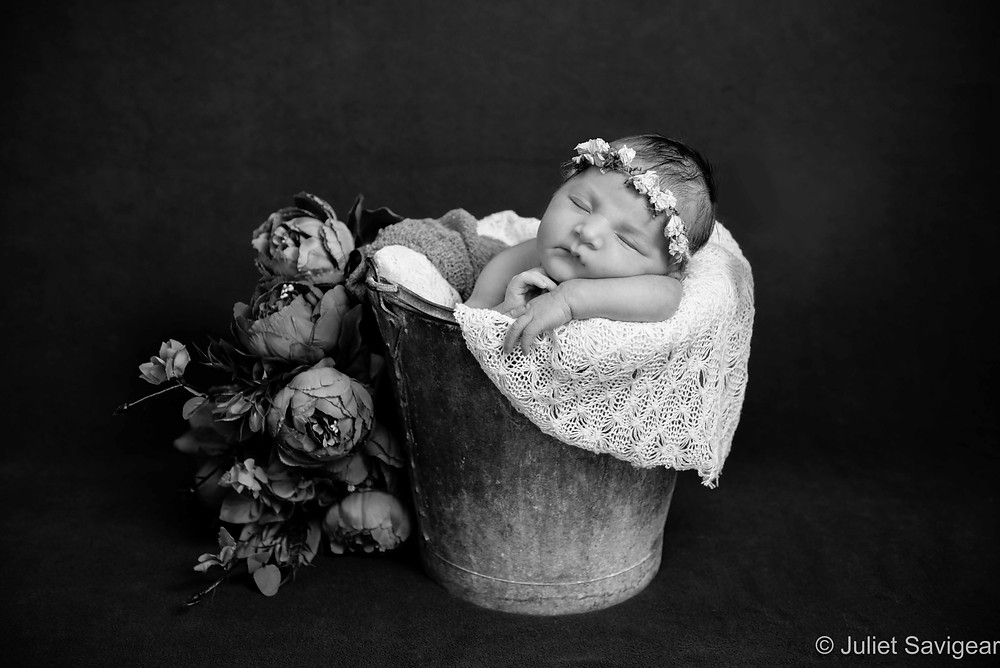 Baby girl sleeping in a bucket with flowers